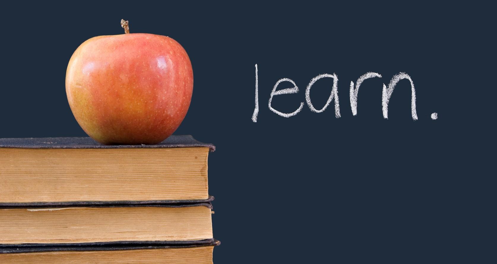 """""""learn"""" written on blackboard with apple, books"""
