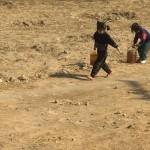 Bambini impiegati nel trasporto d'acqua nelle comunità rurali.
