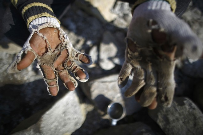 A construction worker shows his torn gloves as he carves stones while building a hotel in Namche in Solukhumbu District