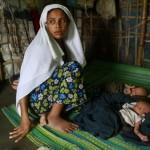 """Sinnuyar Baekon, 25 anni, è tra i molti musulmani Rohungya che vivono negli squallidi campi di Myanmar dopo essere stati sfollati dai disordini religiosi. Baekon proviene dallo stato del Rakhine, dove casa sua fu bruciata negli scontri religiosi scoppiati nel giugno 2012. Da lì fuggì al campo di Dapain, campo non registrato, dove tutt'ora risiede senza ricevere alcun supporto, ne dal Governo ne dall'Ong internazionali. Suo marito la lasciò prima che desse alla luce due gemelli, e ora fa del proprio meglio per dar loro qualcosa da mangiare ogni giorno. """"Non mi ha detto niente prima di partire"""", ha commentato Baekon, """"Adesso non ho ne soldi, ne cibo. Dopo che mangio un pasto non ho nient'altro da mangiare per una settimana."""""""