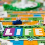 I giochi da tavolo spesso hanno origini antiche, e nel caso di The Game of Life parliamo addirittura del 1861 quando Milton Bradley, pioniere dei moderni game designer, inventò questo passatempo ispirandosi a un gioco di importazione che gli era stato donato da un amico. In questo gioco è necessario prendere decisioni finanziarie e fare investimenti come, ad esempio, quale lavoro scegliere o quale casa comprare. Come accade anche nel Monopoli, ogni casella può nascondere insidie o eventi lieti: a seconda della fortuna, ci si troverà a guadagnare o spendere denaro, andando a modificare il nostro capitale disponibile, che poi rappresenta in qualche modo la misura del nostro successo rispetto agli altri giocatori. Ci capiterà di scegliere tra studio o lavoro, tra carriere diametralmente opposte, oppure di sposarci e avere dei figli, con le spese che tutto ciò comporta. Al termine del tabellone, potremo ritirarci a vita privata e stare a guardare cosa riescono a fare i nostri avversari prima di raggiungerci…