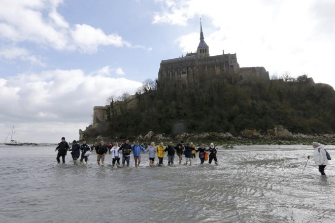 Tourists walk through retreating waters with a bay guide around the Mont Saint-Michel off France's Normandy coast