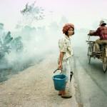 A Sumatra, una donna indonesiana attende di attraversare la strada principale da Palembang a lahat , il 10 settembre, mentre un risciò avanza nel grigiore del fumo denso.