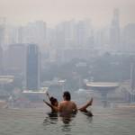 Una coppia si rilassa in una piscina con vista sullo skyline di Singapore coperto dalla foschia, il 22 ottobre 2010. Ai tempi Singapore, interamente ricoperta da una nebbia fumosa, implorò la vicina Indonesia affinché spegnesse i fuochi accesi per il disboscamento delle foreste.