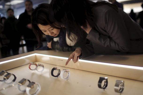 Customers look at an Apple Watch after it went on display at an Apple Store in downtown Shanghai