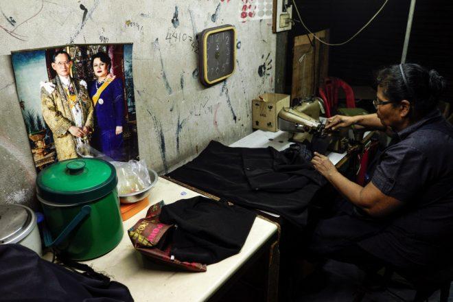 Un sarto lavora su degli abiti neri. Foto REUTER